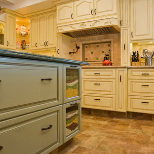 This is an example of a large traditional u-shaped separate kitchen in San Diego with a farmhouse sink, raised-panel cabinets, yellow cabinets, granite benchtops, beige splashback, stone tile splashback, panelled appliances, porcelain floors and with island.
