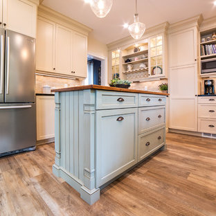 Mid-sized traditional separate kitchen in New York with a farmhouse sink, recessed-panel cabinets, beige cabinets, soapstone benchtops, beige splashback, travertine splashback, stainless steel appliances, vinyl floors, with island, brown floor and black benchtop.