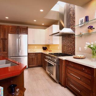 Immagine di una cucina minimal di medie dimensioni con lavello a doppia vasca, ante con bugna sagomata, ante in legno scuro, top in superficie solida, elettrodomestici in acciaio inossidabile, pavimento in gres porcellanato, penisola e top rosso