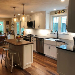 Design ideas for a mid-sized country l-shaped eat-in kitchen in Boston with a farmhouse sink, shaker cabinets, white cabinets, quartz benchtops, white splashback, stainless steel appliances, medium hardwood floors, with island, multi-coloured floor and black benchtop.