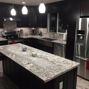 Modelo de cocina en L, moderna, de tamaño medio, abierta, con fregadero bajoencimera, puertas de armario negras, encimera de granito, salpicadero verde, salpicadero de travertino, electrodomésticos de acero inoxidable, una isla y suelo gris