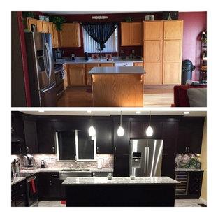 他の地域の中くらいのモダンスタイルのおしゃれなキッチン (アンダーカウンターシンク、黒いキャビネット、御影石カウンター、グレーのキッチンパネル、トラバーチンのキッチンパネル、シルバーの調理設備、グレーの床) の写真