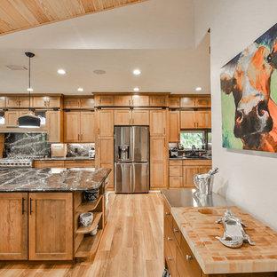 マイアミの大きいトラディショナルスタイルのおしゃれなキッチン (アンダーカウンターシンク、落し込みパネル扉のキャビネット、中間色木目調キャビネット、オニキスカウンター、黒いキッチンパネル、石スラブのキッチンパネル、シルバーの調理設備、磁器タイルの床、茶色い床、黒いキッチンカウンター) の写真