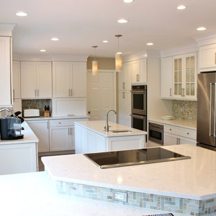 Inspiration for a large transitional eat-in kitchen in DC Metro with an undermount sink, white cabinets, beige splashback, stainless steel appliances, multiple islands, shaker cabinets, quartzite benchtops, stone tile splashback, porcelain floors and brown floor.