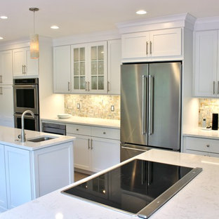Design ideas for a large transitional kitchen in DC Metro with an undermount sink, white cabinets, beige splashback, stainless steel appliances, multiple islands, shaker cabinets, quartzite benchtops, stone tile splashback, porcelain floors and brown floor.