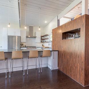 サンフランシスコの大きいコンテンポラリースタイルのおしゃれなキッチン (ドロップインシンク、フラットパネル扉のキャビネット、黄色いキャビネット、白いキッチンパネル、シルバーの調理設備の、濃色無垢フローリング) の写真