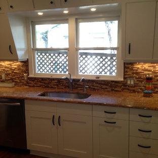 オースティンの中サイズのエクレクティックスタイルのおしゃれなキッチン (アンダーカウンターシンク、落し込みパネル扉のキャビネット、白いキャビネット、御影石カウンター、茶色いキッチンパネル、ボーダータイルのキッチンパネル、シルバーの調理設備の、無垢フローリング) の写真