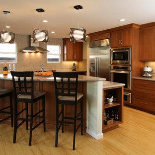 Пример оригинального дизайна: большая угловая кухня в современном стиле с фасадами в стиле шейкер, фасадами цвета дерева среднего тона, бежевым фартуком, техникой из нержавеющей стали, полом из бамбука, островом, столешницей из кварцевого композита, обеденным столом, врезной раковиной, фартуком из керамической плитки, коричневым полом и бежевой столешницей