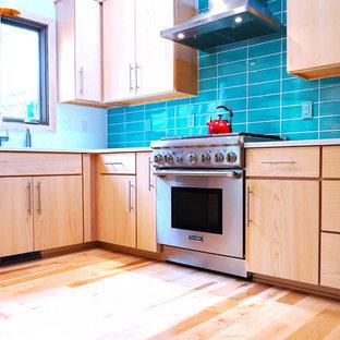 Mittelgroße Mid-Century Wohnküche mit Einbauwaschbecken, flächenbündigen Schrankfronten, hellbraunen Holzschränken, Quarzwerkstein-Arbeitsplatte, Küchenrückwand in Blau, Küchengeräten aus Edelstahl, hellem Holzboden, Halbinsel und weißer Arbeitsplatte in Sonstige