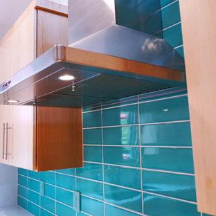 他の地域の中サイズのミッドセンチュリースタイルのおしゃれなキッチン (ドロップインシンク、フラットパネル扉のキャビネット、中間色木目調キャビネット、クオーツストーンカウンター、青いキッチンパネル、シルバーの調理設備の、淡色無垢フローリング、白いキッチンカウンター) の写真