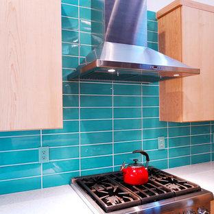 他の地域の中くらいのコンテンポラリースタイルのおしゃれなキッチン (ドロップインシンク、フラットパネル扉のキャビネット、中間色木目調キャビネット、クオーツストーンカウンター、青いキッチンパネル、シルバーの調理設備、淡色無垢フローリング、白いキッチンカウンター) の写真