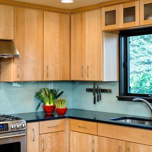 Bild på ett mellanstort funkis kök, med en undermonterad diskho, släta luckor, skåp i ljust trä, bänkskiva i kvarts, glaspanel som stänkskydd, rostfria vitvaror, korkgolv och en köksö