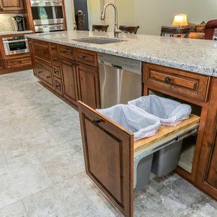 ヒューストンのラスティックスタイルのおしゃれなキッチン (レイズドパネル扉のキャビネット、中間色木目調キャビネット、シルバーの調理設備の、アンダーカウンターシンク、御影石カウンター、グレーのキッチンパネル、石スラブのキッチンパネル、トラバーチンの床) の写真