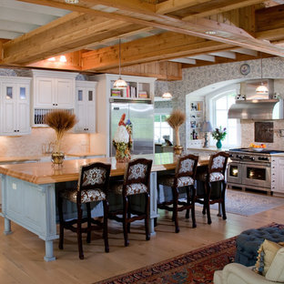 Traditional l-shaped open plan kitchen in Cincinnati with a farmhouse sink, recessed-panel cabinets, beige cabinets, wood benchtops, beige splashback, stone tile splashback and stainless steel appliances.
