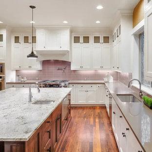 Bild på ett avskilt, stort funkis grå grått l-kök, med en undermonterad diskho, luckor med infälld panel, vita skåp, bänkskiva i kvarts, rosa stänkskydd, stänkskydd i keramik, rostfria vitvaror, mellanmörkt trägolv, en köksö och brunt golv