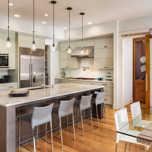 Design ideas for a medium sized contemporary l-shaped kitchen/diner in San Francisco with flat-panel cabinets, white splashback, stainless steel appliances, an island, grey cabinets, a submerged sink, marble worktops, ceramic splashback and light hardwood flooring.