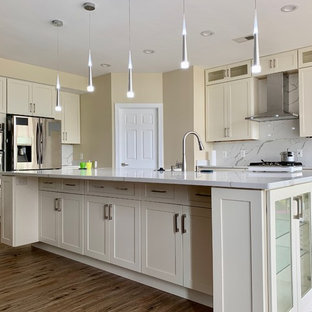 Photo of a large modern l-shaped eat-in kitchen in DC Metro with a double-bowl sink, shaker cabinets, white cabinets, quartz benchtops, white splashback, stone slab splashback, stainless steel appliances, vinyl floors, with island, brown floor and white benchtop.