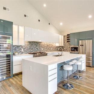 他の地域の中くらいのコンテンポラリースタイルのおしゃれなキッチン (アンダーカウンターシンク、フラットパネル扉のキャビネット、白いキャビネット、珪岩カウンター、マルチカラーのキッチンパネル、ボーダータイルのキッチンパネル、シルバーの調理設備、無垢フローリング、茶色い床、白いキッチンカウンター) の写真