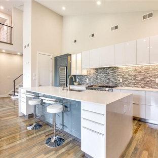 Mittelgroße Moderne Wohnküche in U-Form mit Unterbauwaschbecken, flächenbündigen Schrankfronten, weißen Schränken, Quarzit-Arbeitsplatte, bunter Rückwand, Rückwand aus Stäbchenfliesen, Küchengeräten aus Edelstahl, braunem Holzboden, Kücheninsel, braunem Boden und weißer Arbeitsplatte in Sonstige