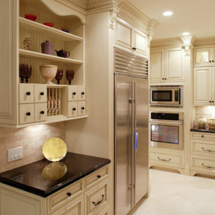 Mid-sized traditional u-shaped open plan kitchen in Los Angeles with a farmhouse sink, recessed-panel cabinets, beige cabinets, limestone benchtops, multi-coloured splashback, ceramic splashback, stainless steel appliances, marble floors, with island, multi-coloured floor and beige benchtop.