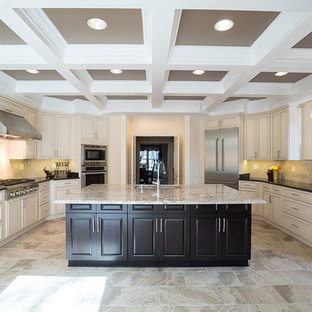 Photo of a large mediterranean u-shaped kitchen in DC Metro with raised-panel cabinets, beige cabinets, marble benchtops, beige splashback, stone tile splashback, stainless steel appliances, marble floors, with island and beige floor.