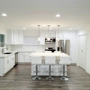 Cette image montre une grand cuisine américaine minimaliste en L avec un placard à porte shaker, des portes de placard blanches, un plan de travail en quartz, un îlot central, un plan de travail turquoise, un électroménager en acier inoxydable, un évier intégré, sol en stratifié et un sol gris.