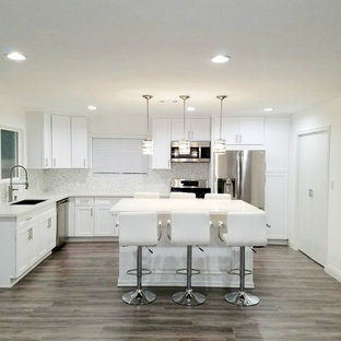 Inspiration for a large modern l-shaped eat-in kitchen in Seattle with shaker cabinets, white cabinets, quartzite benchtops, with island, turquoise benchtop, stainless steel appliances, an integrated sink, laminate floors and grey floor.