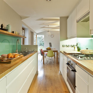 Inspiration for a retro galley enclosed kitchen in Other with stainless steel appliances, wood worktops, a built-in sink, flat-panel cabinets, white cabinets and glass sheet splashback.