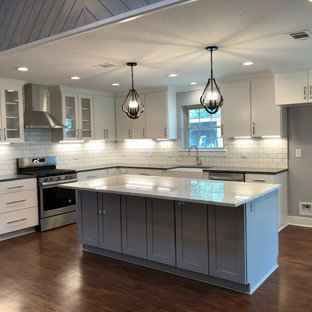 Photo of a mid-sized country l-shaped eat-in kitchen in Austin with a farmhouse sink, shaker cabinets, white cabinets, quartzite benchtops, white splashback, subway tile splashback, stainless steel appliances, vinyl floors, with island, brown floor and white benchtop.