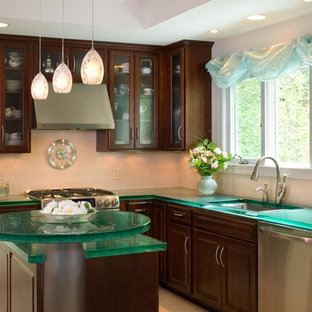 Photo of a contemporary l-shaped kitchen/diner in Orlando with a built-in sink, medium wood cabinets, stainless steel appliances, an island, glass-front cabinets, glass worktops and green worktops.