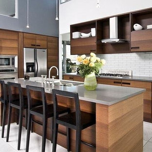 Photo of a large country eat-in kitchen in Los Angeles with a double-bowl sink, dark wood cabinets, zinc benchtops, white splashback, stainless steel appliances, porcelain floors, with island and glass tile splashback.