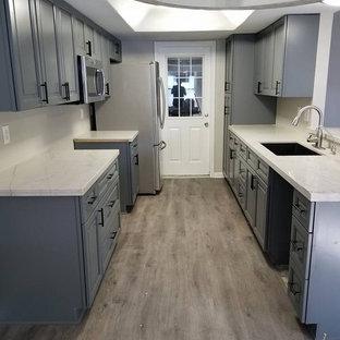 Geschlossene, Zweizeilige, Kleine Klassische Küche ohne Insel mit Unterbauwaschbecken, profilierten Schrankfronten, grauen Schränken, Quarzit-Arbeitsplatte, grauem Boden und weißer Arbeitsplatte in Houston
