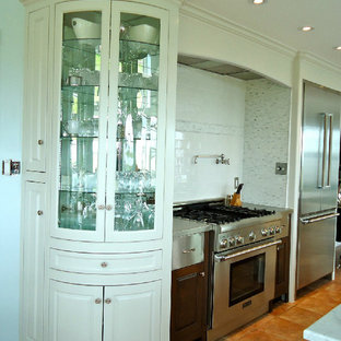 This is an example of a mid-sized transitional u-shaped eat-in kitchen in Vancouver with a farmhouse sink, beaded inset cabinets, white cabinets, marble benchtops, white splashback, stone tile splashback, stainless steel appliances, ceramic floors and with island.