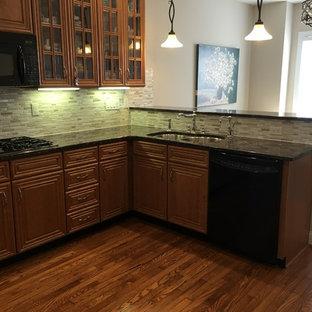 Idee per una cucina chic di medie dimensioni con lavello a doppia vasca, ante con bugna sagomata, top in granito, paraspruzzi grigio, paraspruzzi con piastrelle a listelli, elettrodomestici neri, pavimento in compensato, una penisola, ante in legno scuro e pavimento marrone