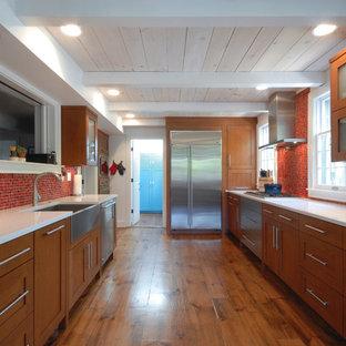 デトロイトのコンテンポラリースタイルのおしゃれなキッチン (赤いキッチンパネル、モザイクタイルのキッチンパネル、エプロンフロントシンク、シェーカースタイル扉のキャビネット、中間色木目調キャビネット、シルバーの調理設備の) の写真