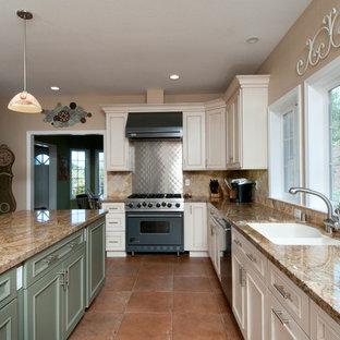 На фото: кухня в классическом стиле с столешницей из гранита, техникой из нержавеющей стали и фартуком из травертина с