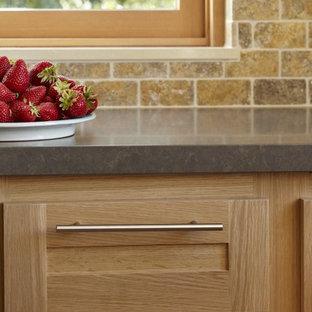 サンフランシスコの広いサンタフェスタイルのおしゃれなキッチン (アンダーカウンターシンク、シェーカースタイル扉のキャビネット、淡色木目調キャビネット、ベージュキッチンパネル、シルバーの調理設備、淡色無垢フローリング、アイランドなし、石タイルのキッチンパネル、茶色い床) の写真