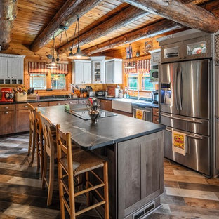 Design ideas for a country l-shaped kitchen in New York with a farmhouse sink, shaker cabinets, dark wood cabinets, timber splashback, stainless steel appliances, with island, multi-coloured floor and black benchtop.