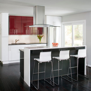 Small contemporary eat-in kitchen designs - Example of a small trendy galley dark wood floor eat-in kitchen design in DC Metro with flat-panel cabinets, red cabinets, white backsplash, an island, an undermount sink, stainless steel appliances, solid surface countertops and ceramic backsplash