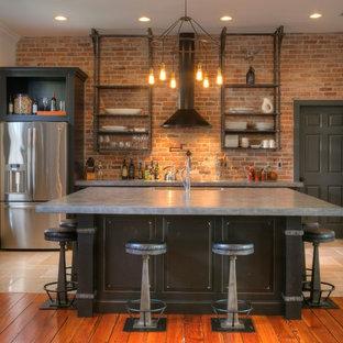 Bild på ett mellanstort industriellt kök, med stänkskydd i tegel, rostfria vitvaror, en köksö, en undermonterad diskho, luckor med infälld panel, bruna skåp, bänkskiva i betong, rött stänkskydd, klinkergolv i keramik och beiget golv