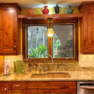 オーランドの中サイズのサンタフェスタイルのおしゃれなキッチン (アンダーカウンターシンク、シェーカースタイル扉のキャビネット、ベージュのキャビネット、御影石カウンター、ベージュキッチンパネル、石タイルのキッチンパネル、シルバーの調理設備の、アイランドなし) の写真