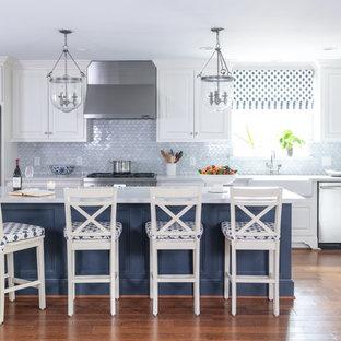 Klassische Küche in L-Form mit Landhausspüle, profilierten Schrankfronten, weißen Schränken, Küchenrückwand in Blau, Küchengeräten aus Edelstahl, braunem Holzboden, Kücheninsel, braunem Boden und weißer Arbeitsplatte in Houston