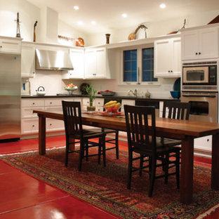 トロントの中くらいのトランジショナルスタイルのおしゃれなキッチン (アンダーカウンターシンク、落し込みパネル扉のキャビネット、白いキャビネット、人工大理石カウンター、白いキッチンパネル、セラミックタイルのキッチンパネル、シルバーの調理設備、コンクリートの床、赤い床) の写真