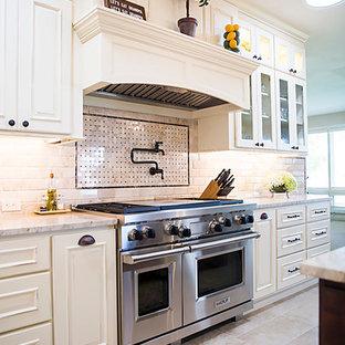 На фото: большая угловая кухня в классическом стиле с обеденным столом, врезной раковиной, фасадами с утопленной филенкой, искусственно-состаренными фасадами, гранитной столешницей, бежевым фартуком, фартуком из цементной плитки, техникой из нержавеющей стали, полом из цементной плитки, островом, серым полом и белой столешницей