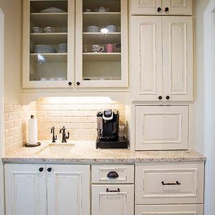 Klassisk inredning av ett mellanstort vit vitt kök, med en undermonterad diskho, luckor med infälld panel, skåp i slitet trä, granitbänkskiva, beige stänkskydd, stänkskydd i cementkakel, rostfria vitvaror, cementgolv och grått golv