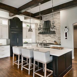Пример оригинального дизайна: угловая кухня в стиле современная классика с фасадами в стиле шейкер, белыми фасадами, серым фартуком, темным паркетным полом, островом и техникой под мебельный фасад