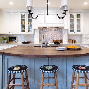 Mittelgroße Klassische Wohnküche in L-Form mit Waschbecken, Schrankfronten mit vertiefter Füllung, weißen Schränken, Arbeitsplatte aus Holz, Küchenrückwand in Blau, Rückwand aus Terrakottafliesen, Elektrogeräten mit Frontblende, Travertin und Kücheninsel in Houston