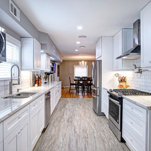 Inspiration for a mid-sized transitional galley eat-in kitchen in Houston with a double-bowl sink, shaker cabinets, white cabinets, marble benchtops, white splashback, subway tile splashback, stainless steel appliances, porcelain floors, no island and grey floor.