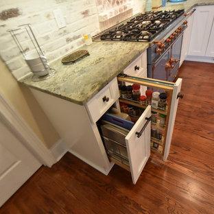 アトランタの中サイズのカントリー風おしゃれなキッチン (エプロンフロントシンク、フラットパネル扉のキャビネット、白いキャビネット、御影石カウンター、マルチカラーのキッチンパネル、レンガのキッチンパネル、カラー調理設備、無垢フローリング、茶色い床、緑のキッチンカウンター) の写真