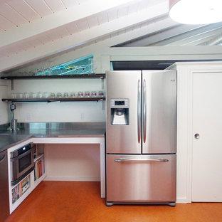 ダラスの中サイズのコンテンポラリースタイルのおしゃれなコの字型キッチン (一体型シンク、フラットパネル扉のキャビネット、白いキャビネット、ステンレスカウンター、メタリックのキッチンパネル、レンガのキッチンパネル、シルバーの調理設備の、リノリウムの床、アイランドなし、オレンジの床) の写真